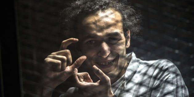 Shawkan, haciendo fotos con sus manos en la zona enrejada desde la que asistía a su juicio, en agosto de 2016.