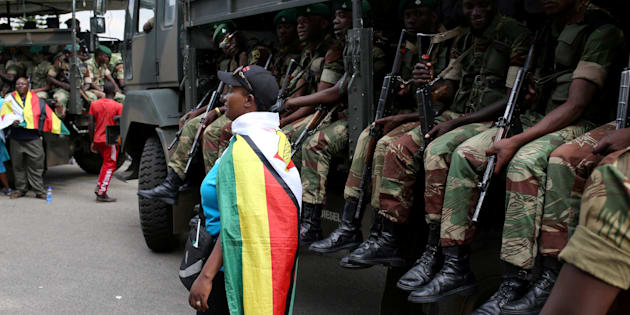 A local poses in front of a military truck after the swearing in of Zimbabwe's President Emmerson Mnangagwa in Harare, Zimbabwe, on November 24, 2017.