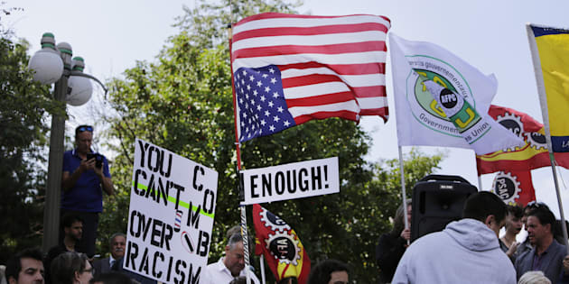 A demonstrator carries an upside-down American flag during an anti-racism rally in front of the U.S. embassy in Ottawa on August 23, 2017.