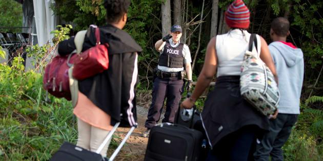 Une agente de la Gendarmerie royale du Canada accueille une famille d'origine haïtienne qui tente d'entrer au Canada par le chemin Roxham, à la frontière avec les États-Unis, en 2017.
