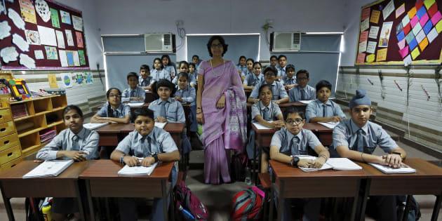 Teacher Archana Shori poses with 7th-grade level students in their classroom at Rukmini Devi Public school in New Delhi, India, September 7, 2015. REUTERS/Adnan Abidi.