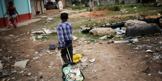 Menino morador em favela volta da escola no Rio de Janeiro.