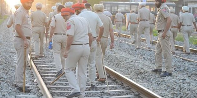 Indian Punjab Police personnel walk at the scene of the accident along railroad tracks in Amritsar on October 20, 2018, after revellers who gathered on the tracks were killed by a moving train on October 19. - A speeding train ran over revellers watching fireworks during a Hindu festival in northern India Friday, killing more than 50 people, with eyewitnesses saying they were given no warning before disaster struck. (Photo by NARINDER NANU / AFP)        (Photo credit should read NARINDER NANU/AFP/Getty Images