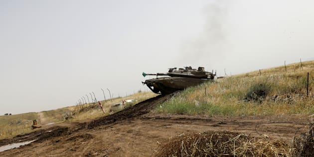 An Israeli tank drives in a field at the Israeli-occupied Golan Heights, Israel May 10, 2018. REUTERS/Ronen Zvulun