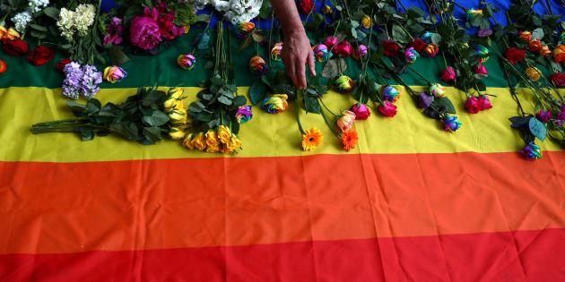 Des manifestants déposent des fleurs sur un drapeau arc-en-ciel alors qu'ils manifestent pour les droits LGBT en Tchétchénie à l'extérieur de l'ambassade russe, à Londres. (REUTERS/Neil Hall)