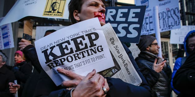 A woman covers her mouth with tape as people take part in a protest outside the New York Times on February 26, 2017 in New York. The White House denied access Frebuary 24. 2017 to an off-camera briefing to several major US media outlets, including CNN and The New York Times. Smaller outlets that have provided favorable coverage however were allowed to attend the briefing by spokesman Sean Spicer. The WHCA said it was 'protesting strongly' against the decision to selectively deny media access. The New York Times said the decision was 'an unmistakable insult to democratic ideals,' CNN called it 'an unacceptable development,' and The Los Angeles Times warned the incident had 'ratcheted up the White House's war on the free press' to a new level.  / AFP / KENA BETANCUR        (Photo credit should read KENA BETANCUR/AFP/Getty Images)