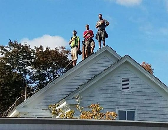 Roofers stop working to stand for national anthem