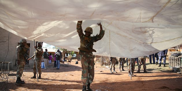 A member of the South African National Defence Force (SANDF) helps set up a tent to be used as a poling station during tense local municipal elections in Vuwani, South Africa's northern Limpopo province, August 3, 2016. REUTERS/Siphiwe Sibeko