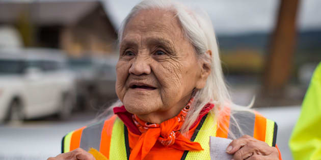 Mabel Todd, 83, of the Nak'azdli First Nation, helps carry a banner as a group of family members and advocates of missing and murdered Indigenous women and girls walk along the so-called Highway of Tears, in Moricetown, B.C., on Monday.