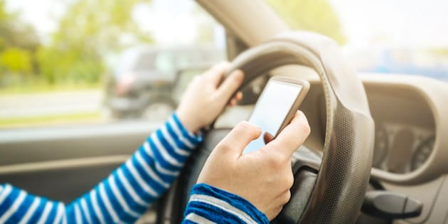 Une femme au volant, téléphone à la main, une attitude dangereuse.