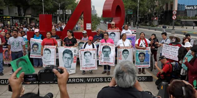 Los familiares posan con imágenes de algunos de los 43 estudiantes de la Escuela Normal Rural de Ayotzinapa Raúl Isidro Burgos frente a un monumento del número 43.