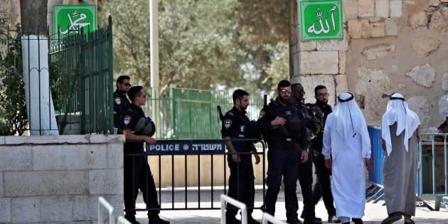 Des Palestiniens et des policiers israéliens à l'entrée de l'esplanade des Mosquées, le 25 juillet à Jérusalem.