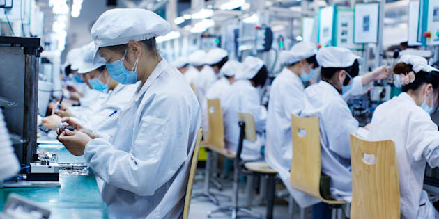 Group of workers at small parts manufacturing factory in China, wearing protective clothing, hats and masks
