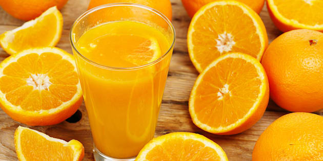 glass of orange juice with oranges on wooden surface
