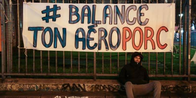"""Un manifestant assis sous une bannière """"# Balance ton Aéroporc"""", jeu de mots faisant référence au phénomène #MeToo et #BalancetonPorc, lors d'un rassemblement à Belleville, au nord de Paris, afin de célébrer l'abandon par le gouvernement du projet d'aéroport à Notre-Dame-des-Landes, le 17 janvier 2018."""