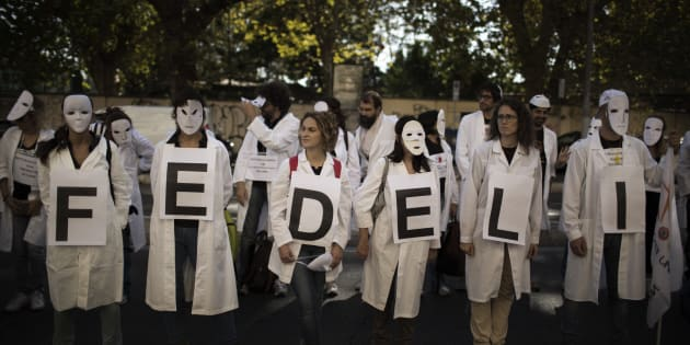 Precarious researchers stand in front of the Ministry of Education during a protest in Rome, on October 4, 2017. Several hundreds of precarious researchers protested against minister of Education Valeria Fedeli asking for indefinite employment contracts after years of precariousness. (Photo by Christian Minelli/NurPhoto via Getty Images)