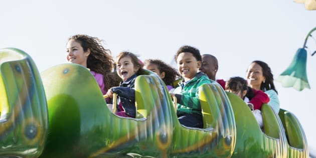 Family on a rollercoaster ride at amusement park.