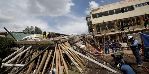 Miembros de un equipo de rescate buscan estudiantes entre los escombros de un edificio derrumbado de la escuela Enrique Rébsamen después de un terremoto.