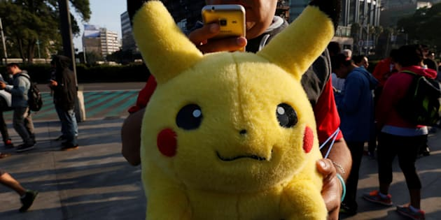 "A man carries stuffed toy of a character from Pokemon, Pikachu, as he plays Pokemon Go during a gathering to celebrate ""Pokemon Day"" in Mexico City August 21, 2016.  REUTERS/Carlos Jasso"
