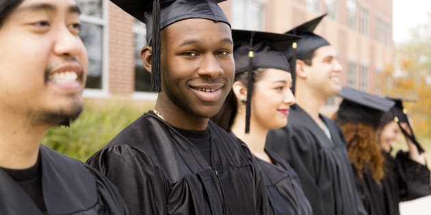 Six, multi-ethnic friend graduates excitedly wait for their name to be called during graduation ceremony. African descent male looks back at camera. School building background.