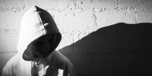 upset teenage boy dressed in hooded jacket leaning against a wall