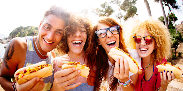 Friends enjoying having hotdogs together