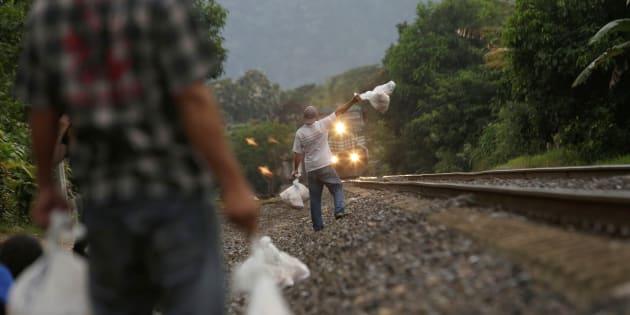"""Voluntarios del grupo """"Las Patronas"""" entregan bolsas de comida a migrantes a bordo de la Bestia."""
