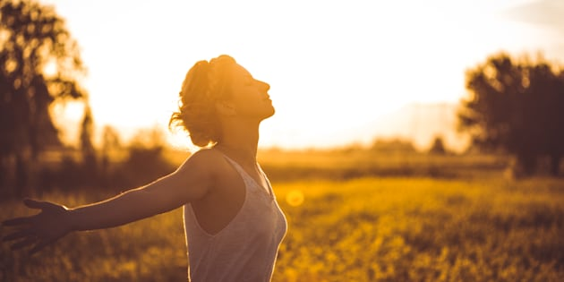 Photo of young woman in nature with arms outstretched