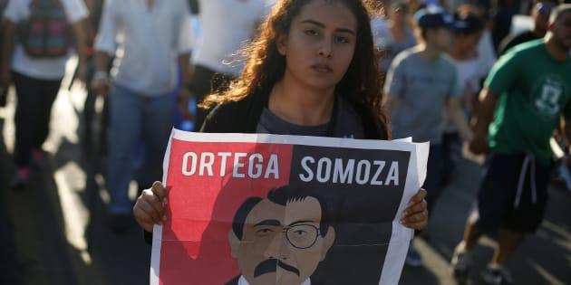 Una manifestante con cartel que compara a Ortega con el dictador Somoza.