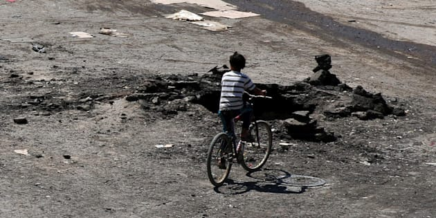 A boy rides a bicycle near a hole in the ground after an airstrike on Sunday in the rebel-held town of Dael, in Deraa Governorate, Syria September 19, 2016.
