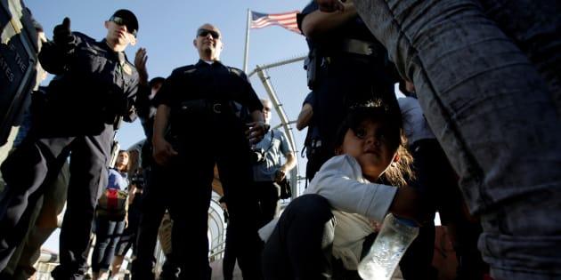 Des familles migrantes qui quittent le Mexique pour fuir la violence écoutent les instructions d'agents de la douane américaine avant d'entrer aux États-Unis pour demander l'asile.
