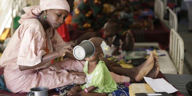 Una madre alimenta a su bebé en un campo de refugiados en Nigeria, África.