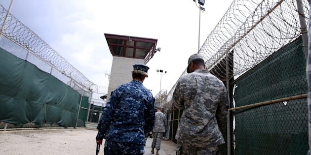 A U.S. Navy sailor (L) walks with soldiers in Joint Task Force Guantanamo's Camp VI at the U.S. Naval Base in Guantanamo Bay, Cuba March 22, 2016.  REUTERS/Lucas Jackson