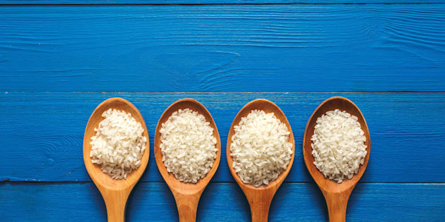Rice on wooden spoon with blue color wood.