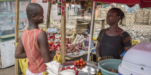 A vegetable retailer sells tomatoes to a customer at the market in Accra on September 08, 2016 in Accra, Ghana.