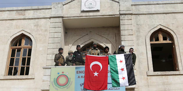 Members of Turkish forces and Free Syrian Army pose with their flags as they are deployed in Afrin, Syria March 18,2018.REUTERS/Khalil Ashawi