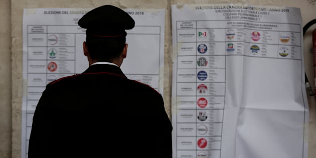 An Italian policeman looks at an electoral poster at a polling station in Rome, Italy March 4, 2018.