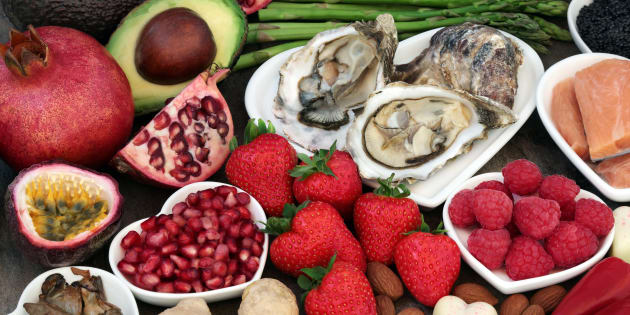Aphrodisiac food in heart shaped dishes and loose over marble background.