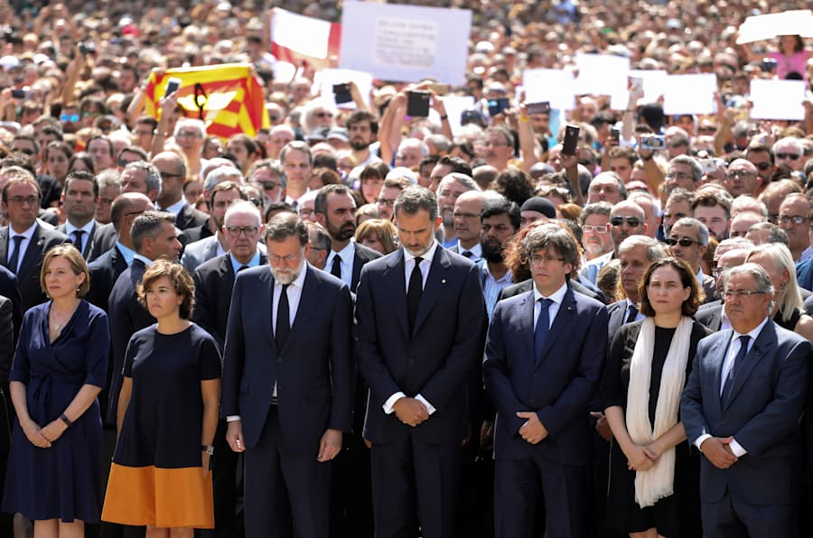 Spain's King Felipe (C) looks down as he stands along politicians including Prime Minister Mariano Rajoy (3rdL) and President of the Generalitat of Catalonia Carles Puigdemont (3rdR) while they observe a minute of silence in Placa de Catalunya, a day after a van crashed into pedestrians at Las Ramblas in Barcelona, Spain August 18, 2017. REUTERS/Sergio Perez