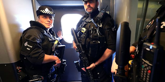 Armed police officers stand in a train at Milton Keynes station, Britain May 25, 2017. Armed police will patrol trains across Britain from Thursday for the first time, British Transport Police said, after the terror threat level was raised to critical following a suicide bombing in Manchester on Monday. REUTERS/Neil Hall
