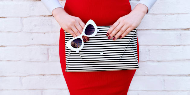 Fashionable woman near white street wall. Retro style and accessories. Trendy outfit red skirt with striped handbag clutch and sunglasses