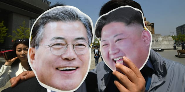 South Korean activists wearing masks of South Korean President Moon Jae-in (L) and North Korean leader Kim Jong Un (R) pose for a photo during a rally to support the upcoming inter-Korean summit