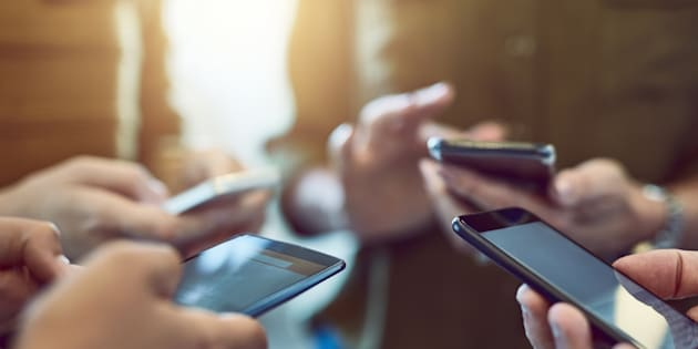 A group of people are seen using smartphones. A non-profit advocacy group is urging the CRTC to launch an inquiry into the sales tactics of Canada's major telecommunications service providers.