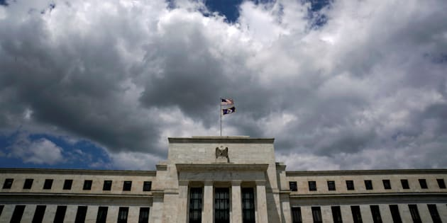 Flags fly over the Federal Reserve Headquarters on a windy day in Washington, U.S., May 26, 2017.