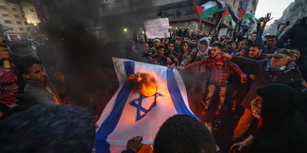 Dei palestinesi intenti a bruciare bandiere americane e israeliane durante una protesta contro il presidente Usa Donald Trump a Gaza ieri, 7 dicembre 2017.