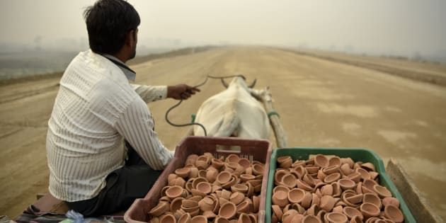 "A man selling traditional earthen lamps ahead of Diwali festival, rides a bullock cart through an under construction road on a foggy day in Greater Noida, near New Delhi, India, Monday, Nov.5, 2018. With air quality reduced to ""very severe"" in the Indian capital region, authorities are bracing for a major Hindu festival featuring massive fireworks that threatens to cloak New Delhi with more toxic smog and dust. (AP Photo/R S Iyer)"
