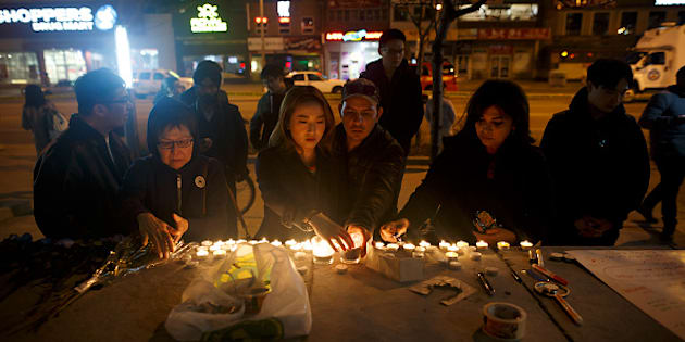 People lay candles and leave messages at a memorial for victims of a crash on Yonge St. at Finch Ave., after a van plowed into pedestrians on April 23, 2018 in Toronto.