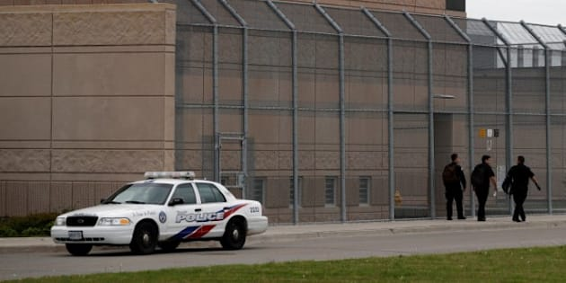 Officers walk by a police car in front of the Toronto South Detention Centre on May 24, 2017.