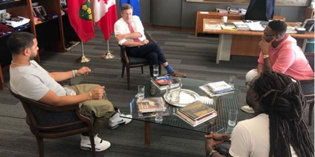 Toronto mayor John Tory met with three prominent members of Toronto's hip-hop community on Friday to discuss gun violence in the city. Clockwise from left: Director X, John Tory, Kardinal Offishall and Taj Critchlow.