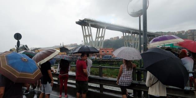 Des curieux observent les opérations de secours après l'effondrement du pont Morandi